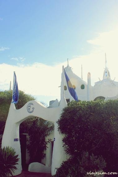 """Tenho muitas viagens sobre as quais ainda não falei aqui no blog ou que ainda tem muita coisa para contar e uma dessas é a que fizemos como """"lua de mel"""" pelo Uruguai após nossa renovação de votos matrimoniais em Buenos Aires. Como estamos no processo de fazer o projeto arquitetônico da nossa casa, fomos dar uma relembrada de locais inspiradores que visitamos em nossas viagens e chegamos a Casapueblo, em Punta del Este, sem dúvidas um lugar inesquecível.  Casapueblo Punta del este o que fazer   Casapueblo é uma casa, um museu, um hotel, restaurante e era também o atelier e obra mais famosa do artista uruguaio Carlos Páez Vilaró, que infelizmente faleceu neste ano. O lugar ficar no bairro de Punta Ballena, logo no início da cidade, no alto de uma encosta, se debruçando sobre o mar e sua arquitetura é única. Construída desde 1958 e pelos 32 anos seguintes, diz-se que foi Casapueblo quem inspirou a famosa música do nosso Vinícius de Morais, que era amigo de Vilaró, """"era uma casa muito engraçada, não tinha teto, não tinha nada"""". O próprio artista chamava o lugar de """"escultura habitável"""".   Casapueblo Punta del este o que fazer   Casapueblo Punta del este o que fazer  Casapueblo Punta del este o que fazer  Casapueblo Punta del este o que fazer   Segundo o site de Casapueblo, a inspiração de Vilaró para sua obra foi a arquitetura instintiva dos homens simples que vão erguendo suas casas de forma """"modelada"""" e sem conhecimentos formais, além de uma influência mediterrânea, uma """"luta aberta com a linha reta e com conceito de forno de pão"""". Também há referências à casa construída pelo pássaro João de Barro, que é encontrado no país.  Visitamos o lugar no inverno, fomos até lá dirigindo, pois tínhamos um carro alugado, e escolhemos o período que todos indicam: o fim da tarde. Dessa forma pudemos ver o pôr do sol dos corredores e varandas criativos da casa e ouvir o famoso Vilaró, em gravação, em sua saudação a esse momento do dia. Na época em que lá estivemos Vilaró ainda era v"""