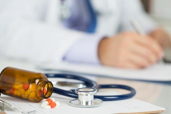 Pode de remédio à frente e médico ao fundo em texto sobre não ficar doente em viagens