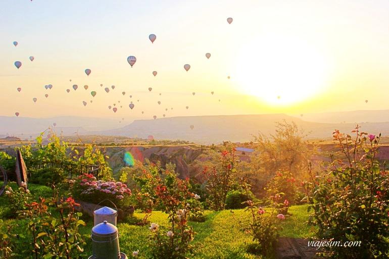 Céu com balões e jardim iluminado na capadócia