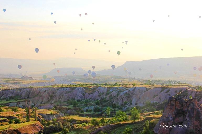 Sol nascendo e balões no céu na Capadócia