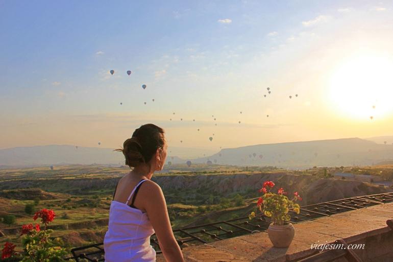 Mulher vendo balões no céu na Capadócia