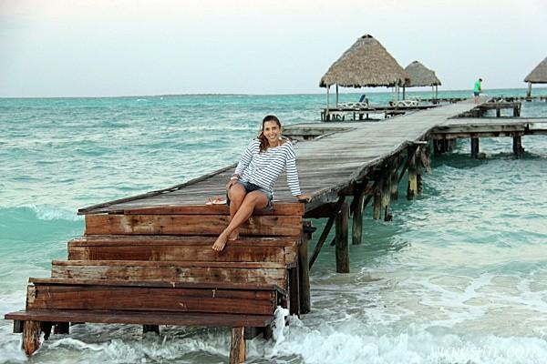 Mulher grávida sentada na ponta de uma passarela sobre o mar do Caribe, em Cuba; ela fez pesquisa sobre seguro viagem para grávida e organizou as informações em seu blog, em um post que explica como funciona o seguro viagem para grávida, como escolher o mais adequado, achar o melhor preço e conseguir um desconto
