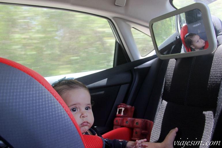 bebê em cadeirinha em carro alugado com espelho retrovisor