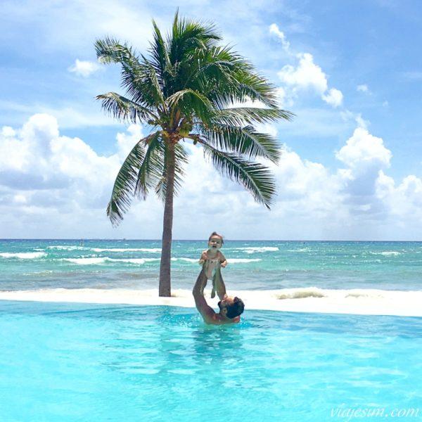 Pai e bebê em piscina de borda infinita em resort em frente à praia em Playa Del Carmen