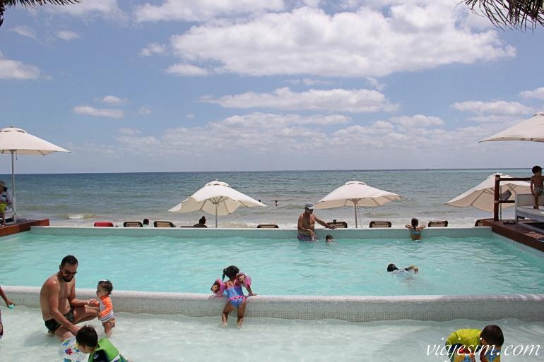 Crianças e bebês em day use de em piscina em frente à praia de um clube em Playa del Carmen