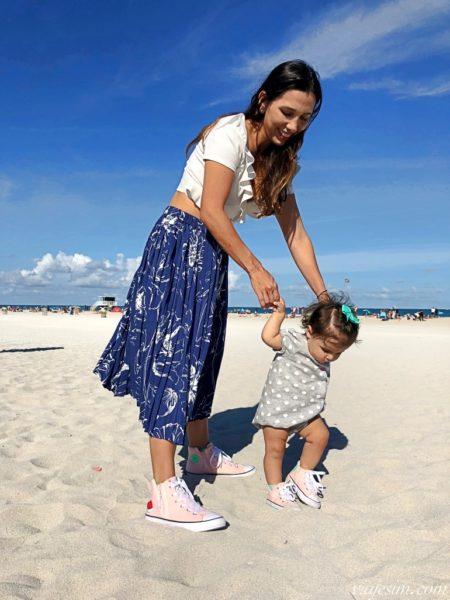 Mãe e filha na areia da praia com tênis all star iguais