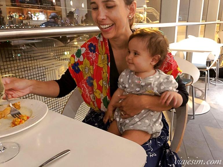 Bebê sorri no colo da mae sentadas à mesa comendo na sala vip Amex em Miami