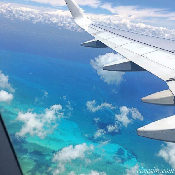 Mar em vários tons de azul visto pela janela do avião em Cancun no México