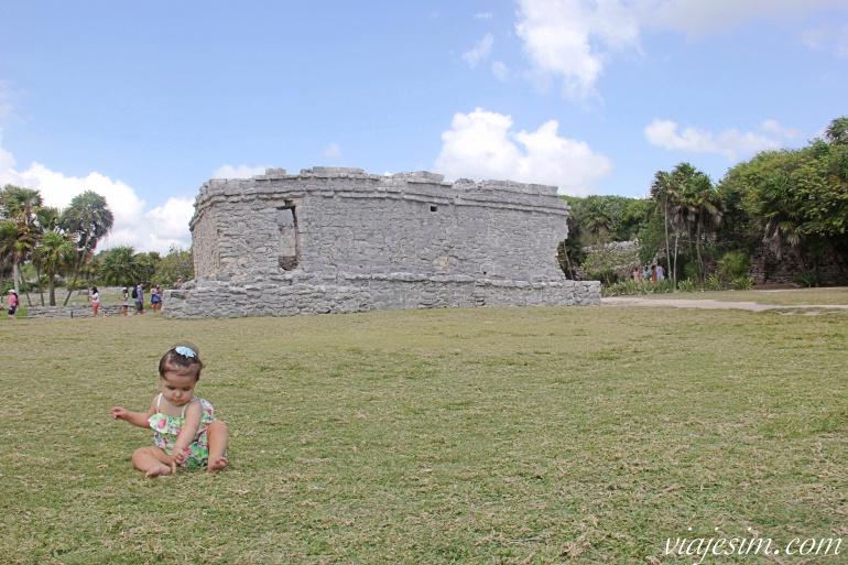 Bebê brinca na grama em frente à uma ruína maia em Tulum, Mexico