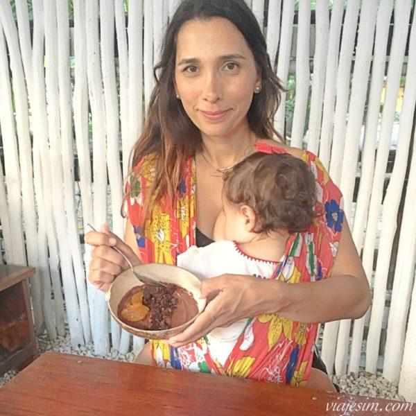 Mãe com pote de sobremesa na mão enquanto bebê mama no sling