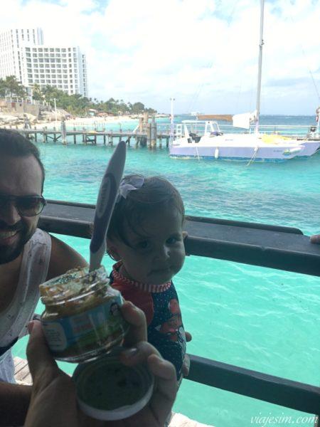 Potinho de comida de bebê e pai e bebê comendo com mar de Cancun ao fundo