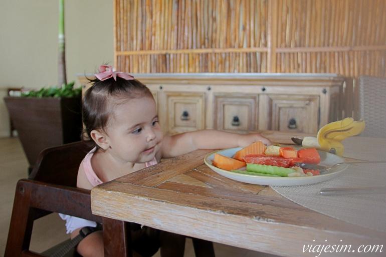 Bebê pega frutas em prato em cima da mesa durante café da manhã em resort em Playa del Carmen