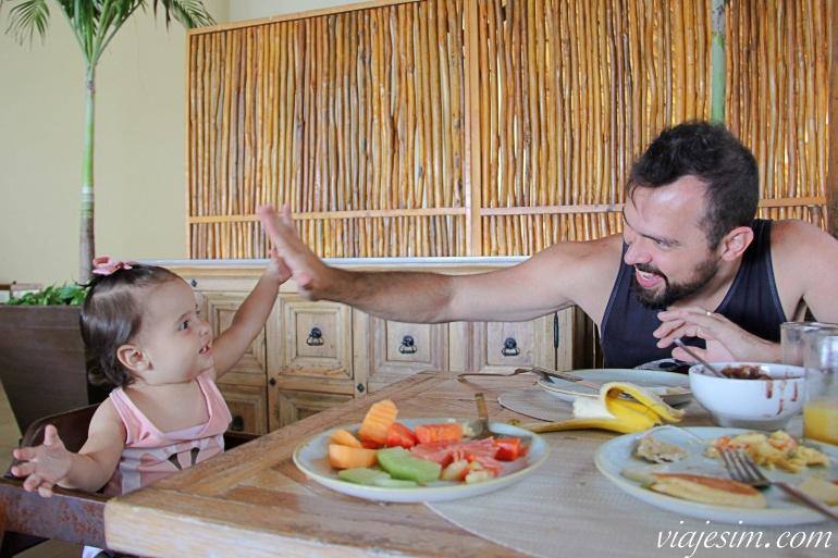 Pai e filha fazendo high five no café da manhã em hotel