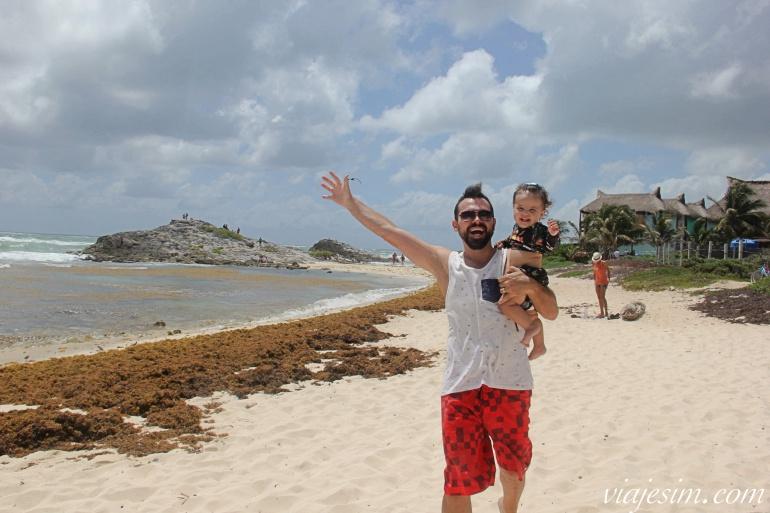 Pai e filha correndo e sorrindo na praia em Tulum