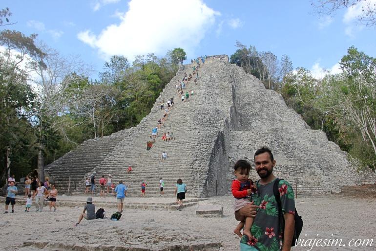 Pai e bebê posam em frente à pirâmide principal de Cobá