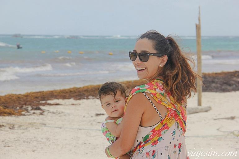 Mãe e bebê no sling sorrindo na areia da praia em Tulum
