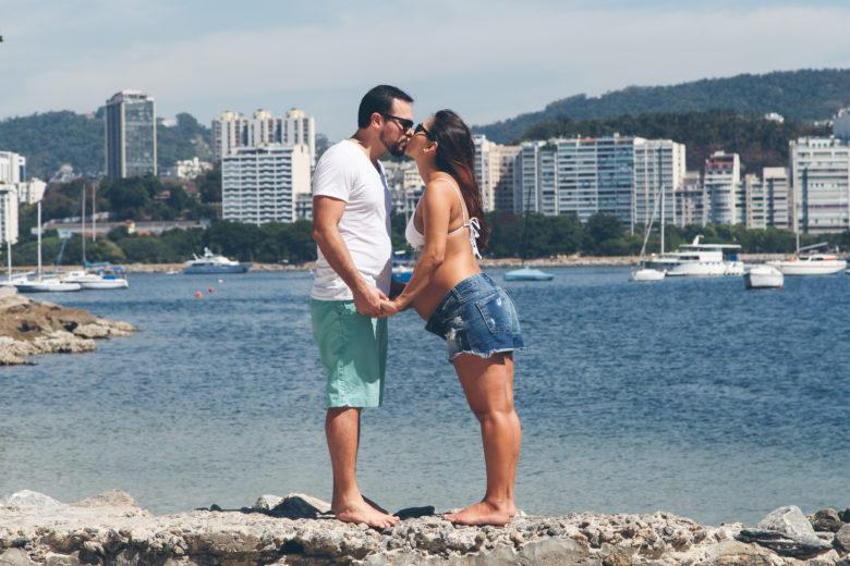 casal com mulher gravida e beija à beira da praia