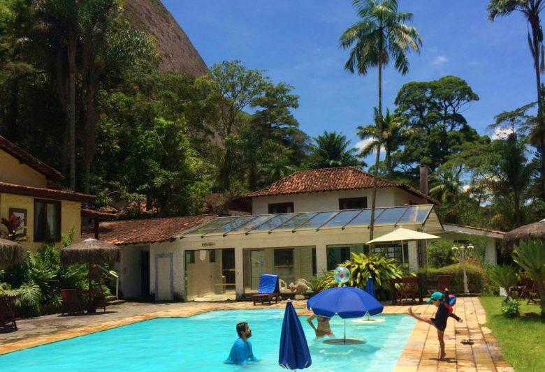 Adulto e criança brincam a beira da piscina em hotel em petrópolis